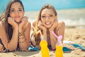 Картинки Пляжи Песке Вдвоем Смотрят Улыбка Руки Шатенки молодая женщина
