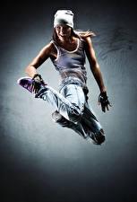Фото Шатенка Танцуют В прыжке Радость В шапке Джинсы Руки девушка