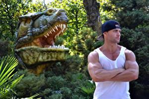 Обои Динозавр Скульптура Мужчины Кусты Головы Кепка Майке Руки Мышцы