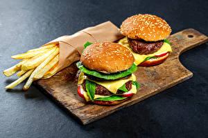 Фотографии Гамбургер Картофель фри Булочки Сыры Котлеты Разделочная доска Двое