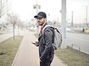 Фото Мужчины Рюкзак Кепка Очки Куртка Размытый фон Наушники