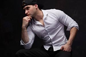 Фотографии Мужчины Черный фон Бейсболка Рубашке Рука Поза Сидящие