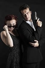 Картинка Мужчины Пистолет 2 Костюме Револьвера Очков Рука Смотрит девушка