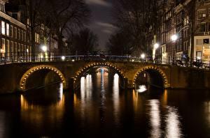 Картинка Мосты Амстердам Нидерланды Ночь Водный канал Уличные фонари Города