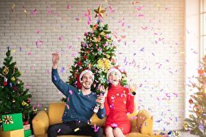 Фотографии Новый год Мужчины Праздники Елка Двое Шапки Сидит Радость Конфетти