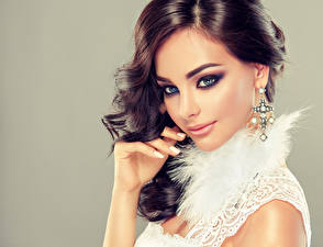 Фотографии Сером фоне Шатенка Косметика на лице Серьги Руки Красивые Прически молодые женщины