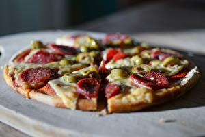 Фотография Пицца Крупным планом Колбаса Оливки Размытый фон Нарезанные продукты Кусок Пища