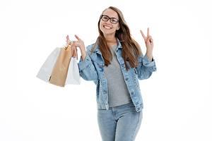 Фотографии Покупки Бумажный пакет Белом фоне Шатенка Очков Улыбка Куртка Руки Джинсов молодая женщина