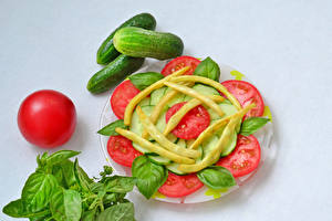 Фотография Овощи Помидоры Огурцы Сером фоне Тарелке Нарезка Базилик душистый