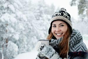 Фотографии Зимние Снега Смотрит Улыбается Шапка Рукавицы Кружки девушка