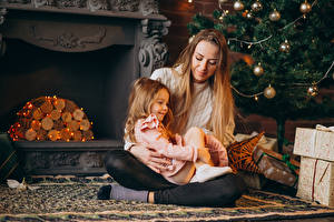 Картинки Новый год Мама Девочки Сидит Шарики Камин Гирлянда Подарки Дети