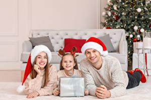 Обои Новый год Мама Мужчины Трое 3 Девочки Шапки Подарки Взгляд Семья Лежит Дети