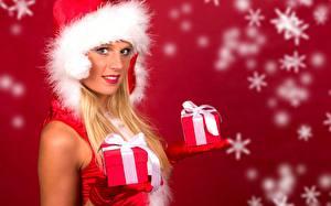 Фото Новый год Снежинка Блондинки Шапка Смотрит Рука Перчатках Подарок Красном фоне девушка