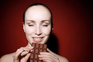 Фотография Шоколад Пальцы Шоколадная плитка Цветной фон Лицо Улыбка Радость молодая женщина
