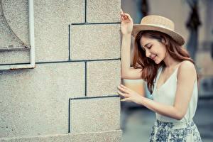 Фотографии Азиатки Позирует Стенка Рука Шляпы Шатенки девушка