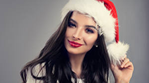 Фотографии Новый год Серый фон Брюнетка Шапки Взгляд Красивые Девушки