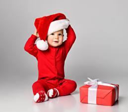 Фото Новый год Серый фон Младенцы Униформа Шапки Подарки Сидит Дети