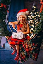 Фотографии Новый год Девочки Улыбка Шапки Сидит Подарки Дети