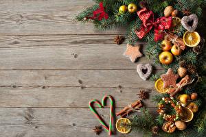 Обои Новый год Леденцы Яблоки Печенье Корица Бадьян звезда аниса Доски Ветки Бантик Шаблон поздравительной открытки