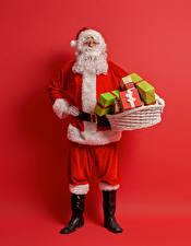 Фото Новый год Красный фон Дед Мороз Униформа Корзинка Подарки Борода