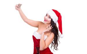Фото Новый год Белым фоном Брюнетка Шапки Улыбается Рука Селфи молодая женщина
