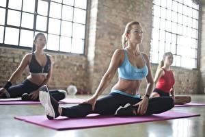Фото Фитнес Спортзале Тренируется Втроем Сидит Блондинки Растяжка упражнение Девушки
