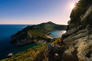 Фото Греция Рассвет и закат Берег Утес Лучи света Korfu Природа