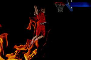Фото Баскетбол Мужчина Пламя На черном фоне Прыгает