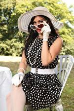 Фото Cassie Clarke Брюнетки Шляпы Очков Платья Сидящие Рука Перчатках девушка