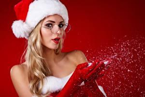 Картинка Рождество Блондинка Шапки Очки Руки Перчатках Красный фон молодая женщина