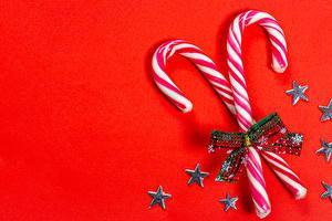 Фотография Рождество Конфеты Леденцы Звездочки Бантики Красном фоне Шаблон поздравительной открытки Пища