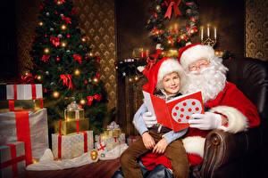 Фотографии Рождество Новогодняя ёлка Подарок Санта-Клаус Мальчик Шапка Сидящие ребёнок