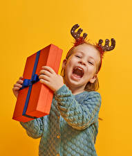 Картинки Рождество Цветной фон Девочки Подарков Радость Рога Дети