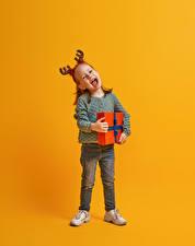Фотографии Рождество Цветной фон Девочки Подарки Радостный Рога