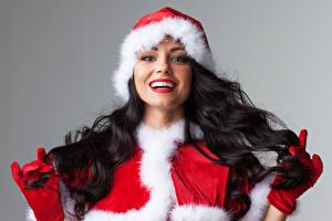 Картинка Новый год Серый фон Брюнеток В шапке Улыбается Смотрит Перчатки Красными губами девушка