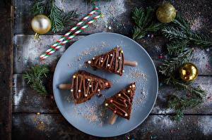Картинки Новый год Пирожное Шоколад Доски Тарелке Трое 3 Новогодняя ёлка Ветка Шарики Еда