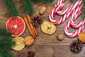 Фотография Новый год Леденцы Корица Орехи Лимоны Грейпфрут Доски Шишка Ветки Пища