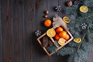 Картинка Рождество Мандарины Орехи Лимоны Доски Ветвь Шишка Пища
