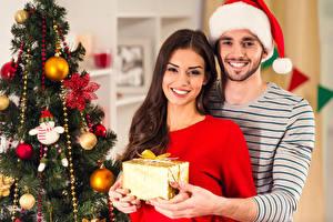 Картинка Рождество Мужчина 2 Шатенки Улыбается Смотрит Шапка Подарок Новогодняя ёлка Рука девушка