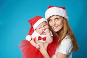 Картинки Рождество Мать Цветной фон Улыбка Шапки Младенец Смотрит ребёнок Девушки