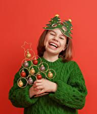 Картинка Новый год Красном фоне Девочки Свитера Новогодняя ёлка Шар Радостный Смех