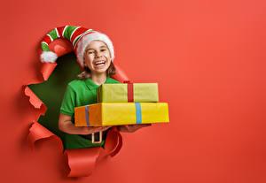 Картинка Рождество Красном фоне Девочка Шапка Подарок Счастье ребёнок