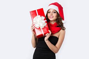 Картинки Новый год Белым фоном Шатенки Шапка Взгляд Подарки Рука молодая женщина
