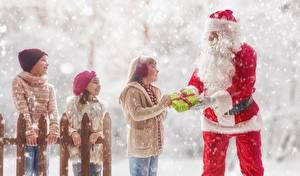 Фотографии Новый год Зима Снега Санта-Клаус Девочка Подарков В шапке Забор Дети