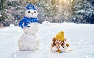 Обои для рабочего стола Рождество Зимние Снеговика Девочки Лежит Улыбка Шапки Шарф Снега ребёнок