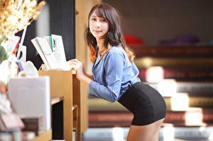 Картинки Азиаты Боке Позирует Офис Секретарши Шатенки Взгляд Юбки молодые женщины