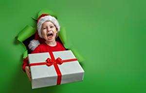 Фотографии Рождество Цветной фон Девочка Подарок Шапка Счастье ребёнок