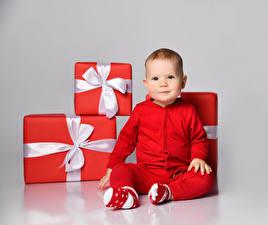 Картинка Рождество Сером фоне Грудной ребёнок Подарок Красная Бантики Смотрит Сидящие ребёнок