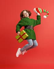 Картинки Новый год Девочка Подарки Платье Шапка Прыгает Улыбка Красный фон Дети
