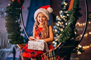 Фотографии Рождество Девочка Шапка Подарок Улыбается Сидящие Смотрит ребёнок